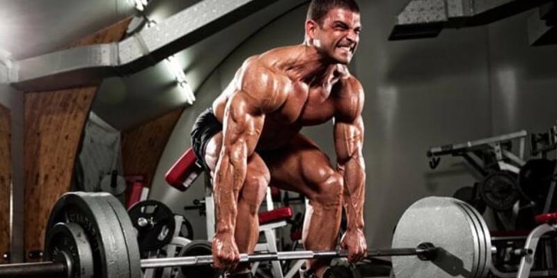 Uomo allena con stacchi bilanciere