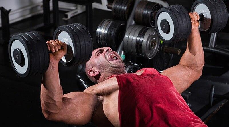 Uomo muscoloso avanzato 2 manubri